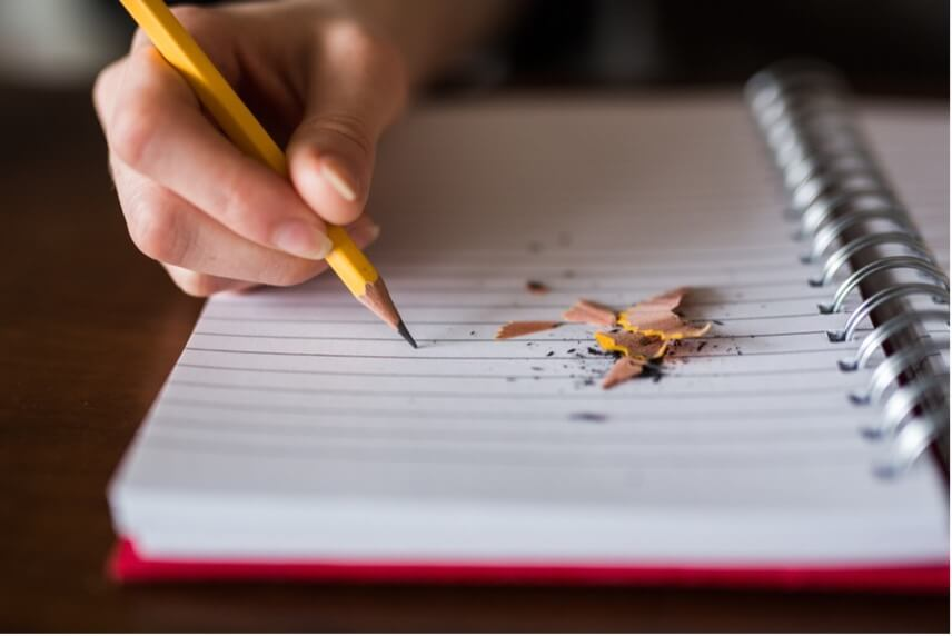 Child writing on a notepad with a pencil, with pencil sharpening debris next to the hand