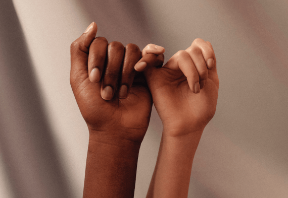 Two gender neutral hands make a pinky promise
